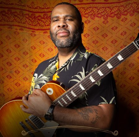 Kirk Fletcher posing with a Gibson Guitar